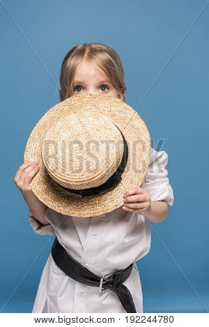 Scared Adorable Little Girl With Straw Boater Isolated On Blue