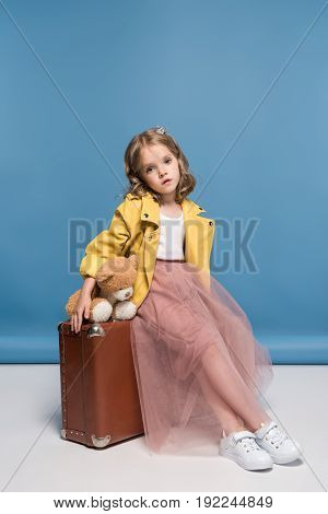 Adorable Little Girl In Pink Skirt Holding Teddy Bear And Sitting On Suitcase In Studio