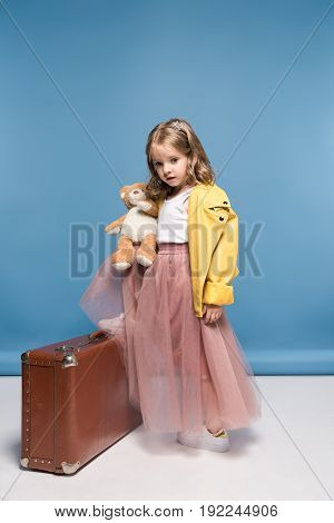 Beautiful Little Girl In Pink Skirt Posing With Teddy Bear And Suitcase
