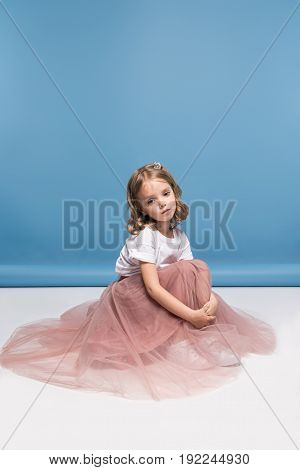 Adorable Little Girl In Pink Skirt Sitting On Floor And Looking At Camera