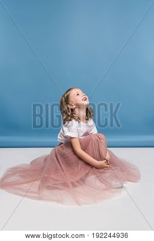 Cute Smiling Little Girl In Pink Skirt Sitting On Floor And Smiling