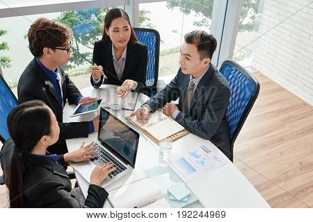 Ambitious group of business people brainstorming on project while having working meeting in modern boardroom, high angle view