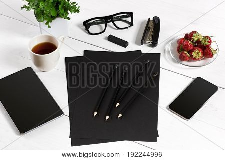 Modern workplace with digital tablet computer and mobile phone, cup of coffee, pen and empty sheet of paper. Top view and copy space for text