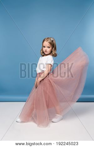 Beautiful Little Girl In Pink Skirt Posing In Studio And Looking At Camera