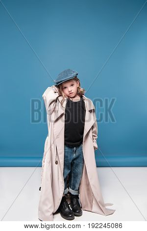 Full Length View Of Adorable Little Girl In Cap Posing In Studio And Looking At Camera