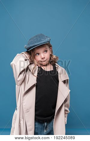 Cute Little Girl In Cap Looking Away Isolated On Blue