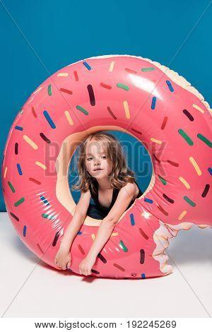 Adorable Little Girl Sitting At Swimming Tube In Shape Of Doughnut