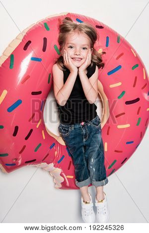 Little Girl Smiling While Lying On Swimming Tube In Form Of Doughnut