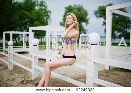 Portrait Of A Stunning Young Female Model In Bikini Posing Next To The White Wooden Fence In The Par