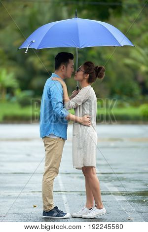 Portrait of young Asian couple embracing tenderly under umbrella on date