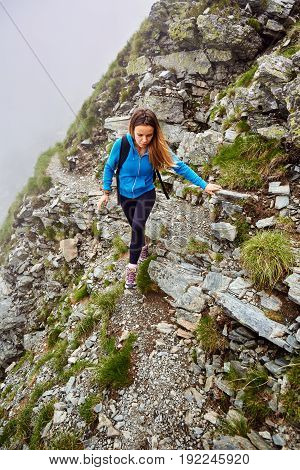 Woman hiker with backpack on a steep trail in the mountains