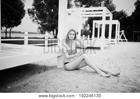 Portrait Of A Gorgeous Young Girl In Bikini Sitting Next To The Gasebo On Sand And Posing. Black And