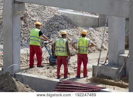 Construction workers doing with vibrating plate compressor on ground leveling at building site