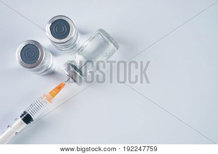 Medical ampoules infusion and syringe with injection isolated on white background with copy space. Ampules with antibiotics closed with caps in a row. Syringe with needle without cap lying on the vial with drug