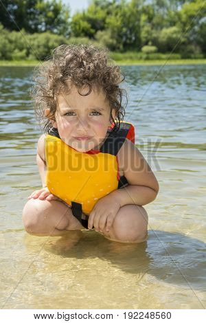 In summer on a bright sunny day a little frightened girl in a life jacket is standing in a river.