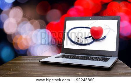 Laptop computer with red heart and stethoscope on white background in screen on wood table with blurred night light bokeh background selective focus heart health care and medical technology concept