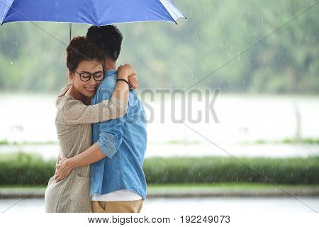 Portrait of loving Asian couple embracing under umbrella on date in rain, copy space