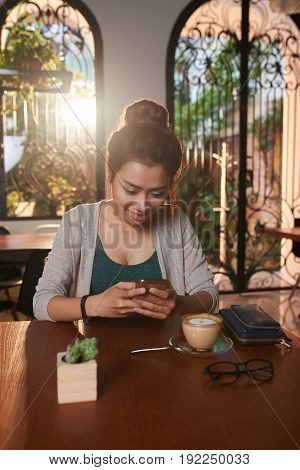 Portrait of pretty Asian woman text messaging in cafe and smiling while waiting for date