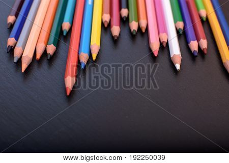 Many Colored Pencils On A Black Stone Slate, Place For Text