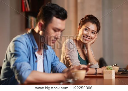 Portrait of smiling Asian woman looking lovingly at stranger man in cafe