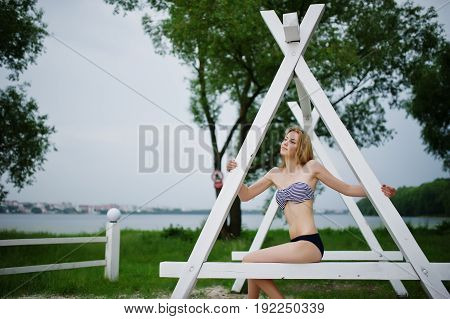 Portrait Of An Attractive Female Model Posing Next To The Triangular White Wooden Construction In Th