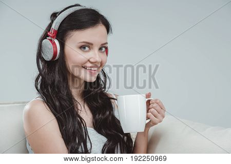 Beautiful Smiling Girl Wearing Headphones And Drinking Tea At Home