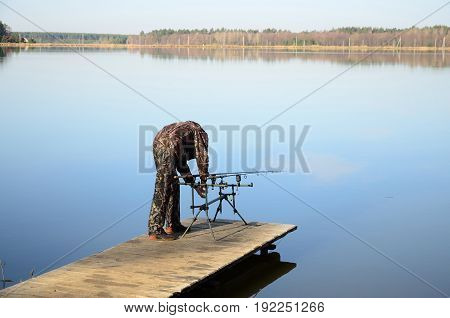 The fisherman installs two feeders on a rod pod with electronic bite alarms on a pier by lake