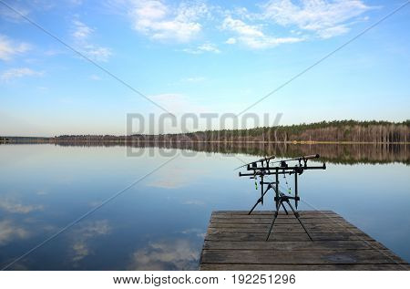 The one rod pod with two feeders with electronic bite alarms on a wooden pier by lake