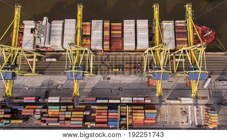 Aerial view of cargo ship unloading in container terminal