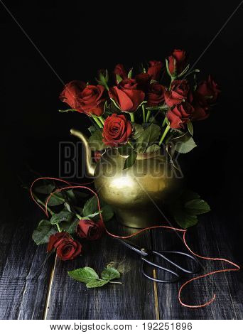 Bouquet of red roses in a copper jar with scissors on a black background, selective focus, concept