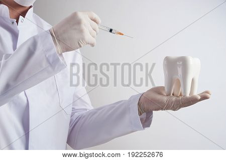 Dentist doing injection into the tooth in dental clinic. Dentist holding a syringe with anesthesia and white healthy prosthetic tooth in the dentist's office on isolate white background.