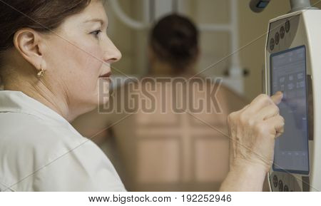 Doctor directs X-ray machine on a patient in hospital