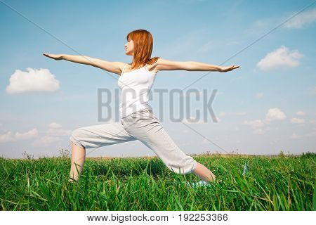 Young girl doing yoga in the park over blue sky