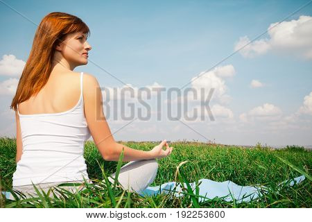 Young girl doing yoga lotus pose in the park over blue sky
