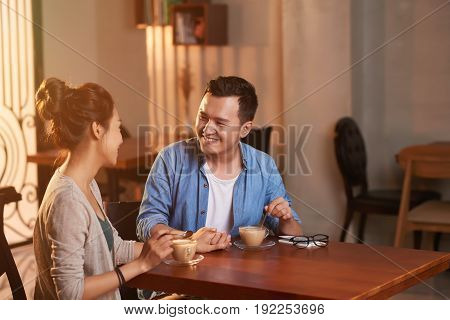Portrait of smiling Asian couple enjoying date in cafe, holding hands and looking at each other with affection