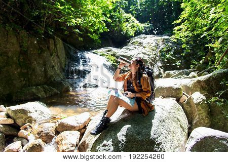 Hiker asia woman drinking water after look binoculars in the water fall background forest. Concept Travel