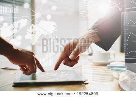 Close-up shot of two businessmen pointing at modern digital tablet lying on table in spacious boardroom, collage