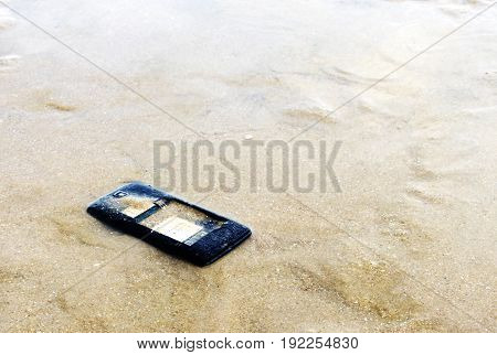 Close Up Of Broken Mobile Phone Drop On Sea Beach With Copy Space, High Contrast, Shallow Depth Of F
