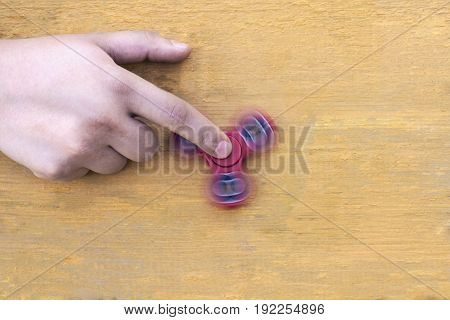 aucasian man holds his finger (hand) Red fidget spinner in motion stress relieving toy on on a yellow wooden background