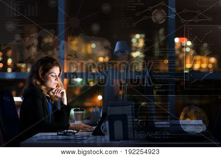 Profile view of attractive middle-aged businesswoman sitting in front of computer and working alone in dark office, panoramic window with night city view on background