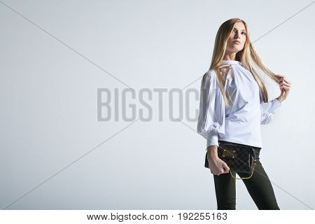 Casual young fashionable woman with a bag in light background
