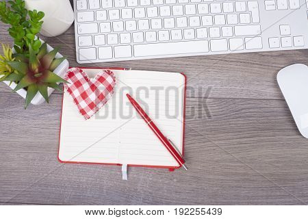 Close-up Work Desk With Keyboard, Open Note, Pen And Beautiful Heart Of Textiles