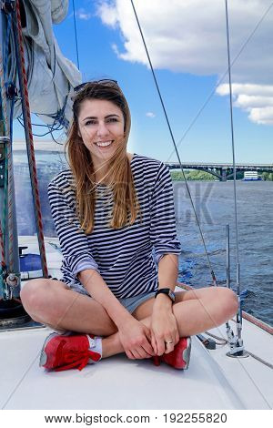 Attractive girl sailing on a yacht in summer day against the blue sky