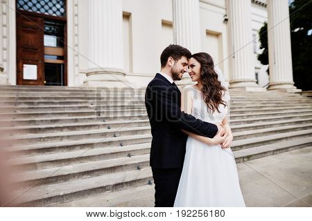 Beautiful bride with curly hair and bridegroom standing close to each other at old city background wedding photo beautiful couple Budapest city.