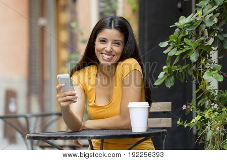 attractive latin woman in her twenties happy and excited on her smart phone
