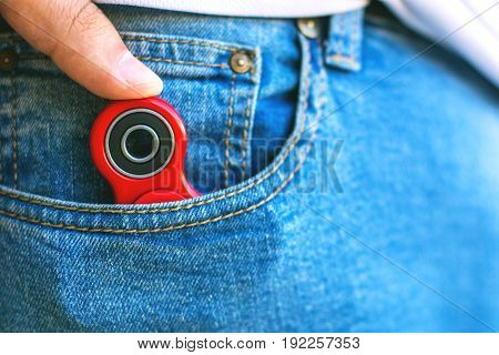 Caucasian man hides his red finger fidget spinner at jeans pocket. Popular spinner gadget in 2017.