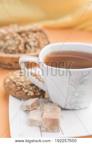 White with a flower pattern cup with tea pieces of brown sugar and homemade cookies with cereals on a white saucer on a warm pastel orange background a vertical frame
