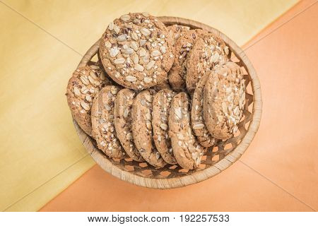 Homemade cookies with cereals and seeds in a wicker basket on a pear-yellow and light orange warm background top view