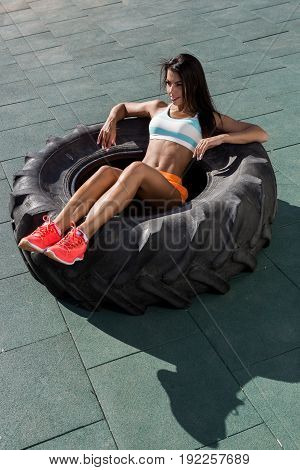 Beautiful young girl with long legs in bright sexy shorts with pretty athlete muscular body rest in big heavy tire. Cross training urban area street gym city exercise routine healthy lifestyle.