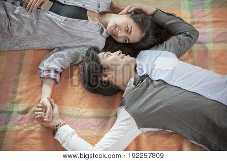 couples of younger asian man and woman relaxing emotion lying in home living room